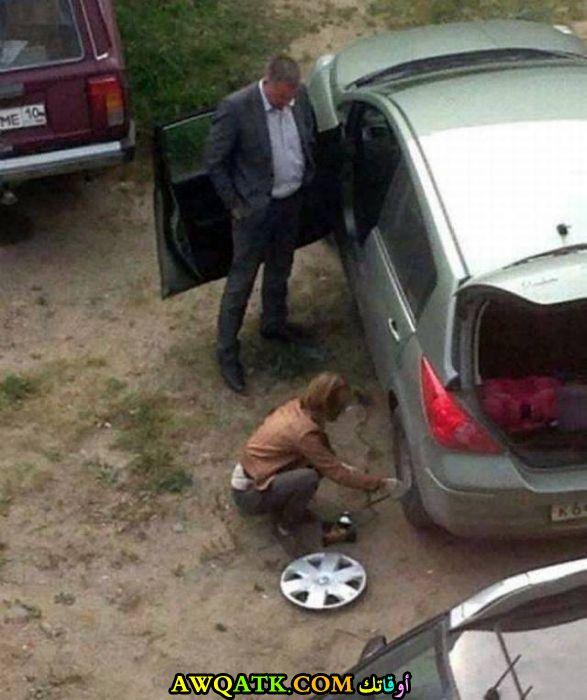 امرأة تغير إطار السيارة